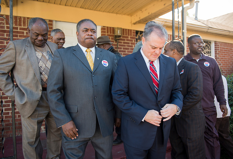 UNITED STATES - NOVEMBER 1: Sen. Mark Pryor, D-Ark., center, buttons up as he prepares to pose for a group photo with local religious leaders after their meeting at the Beautiful Zion Church in West Memphis, Ark., on Saturday, Nov. 1, 2014. (Photo By Bill Clark/CQ Roll Call)