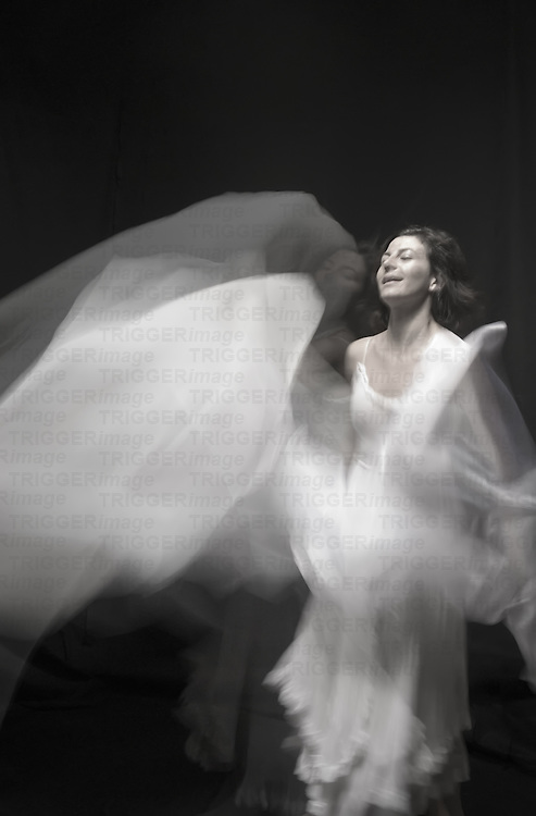 A young woman in a white dress dancing with a white veil