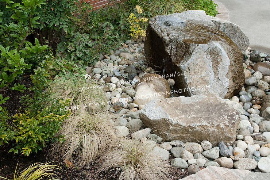 Water cascades over a rock in this garden's water feature.