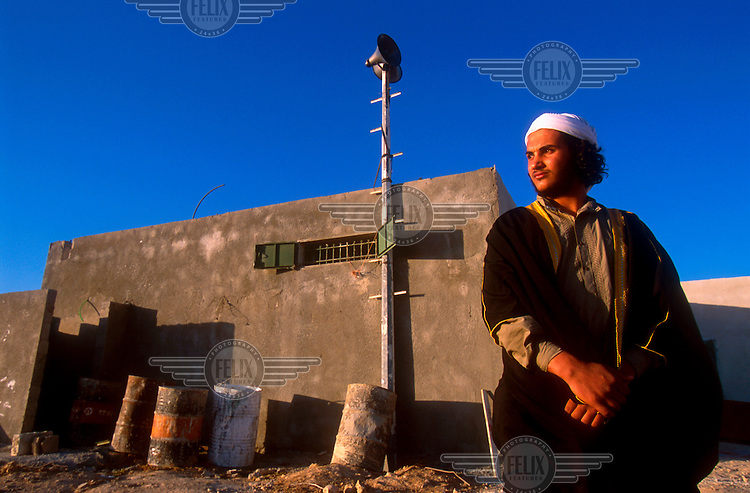 The Imam (a Muslim priest) of the unrecognised Bedouin village of Abu Ajaj stands near the village mosque.  Like many other houses in the village. the mosque is threatened by a demolition order issued by the Israeli authorities. .