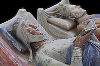 Royal tombs of Eleanor of Aquitaine and King Henry II of England in the nave of the Abbey Church at Fontevraud Abbey, Anjou, France. Eleanor of Aquitaine, 1122-1204, is seen here with her husband King Henry II of England and is reading a book, a symbol of her unusual stature and learning. The Plantagenet rulers were benefactors of the monastery. The effigy is carved in stone and was painted, she wears a crown and nun's wimple and her robes are blue and white. Fontevraud Abbey was founded in 1100 by Robert of Arbrissel and became a double monastery for both monks and nuns, led by an Abbess. The Order was dissolved during the French Revolution. Picture by Manuel Cohen