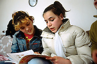 Bosnia and Herzegowina. Republika Serpska. Srebrenica. Two girlfriends read the same schoolbook. On the left, Inisi Hoti is muslim . On the right, Vesna Andric is serb. © 2005 Didier Ruef