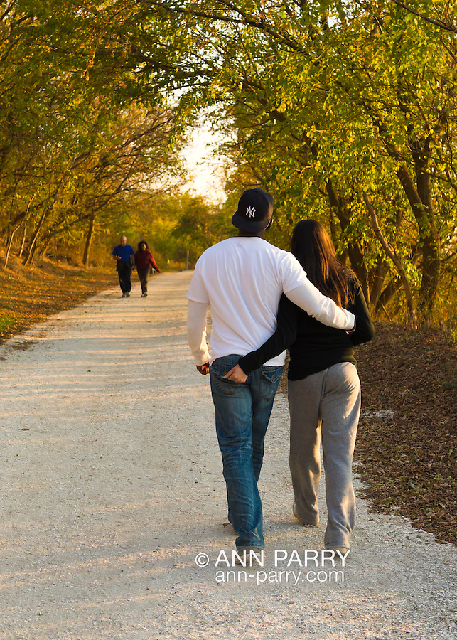 South Merrick, New York, U.S. 29th October 2013. JIMMY EDWARDS, of Bellmore, and TAMI BAQUE, of Freeport, walk on the trail through Levy Park and Preserve during dusk, on the First Anniversary of Superstorm Sandy hitting New York. Long Island's South Shore marshland park, which closed for months due to Sandy's devastation, shows some recovery from the wind and flood damage inflicted on the entire eastern seaboard of America's East Coast.