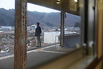 March 24, 2011, Tarou, Morioka City, Iwate Prefecture, Japan - A passenger from the Revitalization Train overlooks the tsunami devastation as the train makes a stop at Tarou Station in Morioka City, Iwate Prefecture. Passengers surveyed the wide-spread tsunami debris and devastation in the aftermath of the 2011 Tohoku Earthquake and Tsunami. (Photo by Kazuhiko Kawamura/AFLO)