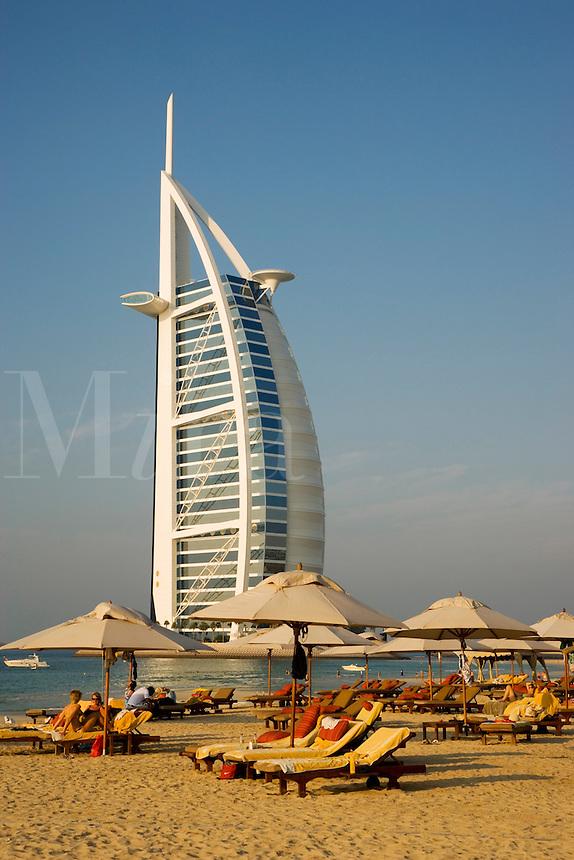 Dubai.  View over beach outside Al Qasr Hotel of Burj al Arab Hotel, architect W.S. Atkins, an icon of Dubai built in the shape of the sail of a dhow, stands on an island off Jumeirah Beach.  .