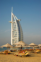 Dubai.  View over beach outside Al Qasr Hotel of Burj al Arab Hotel, architect W.S. Atkins, an icon of Dubai built in the shape of the sail of a dhow, stands on an island off Jumeirah Beach.  .