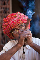 Indian man wearing Rajasthani turban smokes traditional clay pipe in Narlai village in Rajasthan, Northern India
