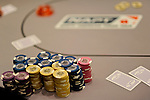 A view of a main event poker table with chips and cards.