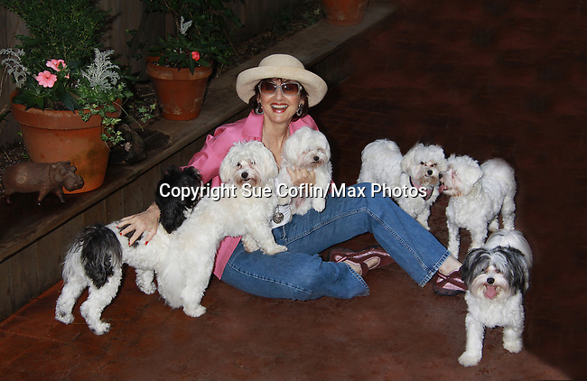 """One Life To Live Robin Strasser poses with her dogs and their puppies on June 30, 2011- Robin Strasser - One Life To Live - with her puppies and mom and dad:.Mother: Bisou - means kiss in French - she's a 6.5 lb MALTESE.Father: Rocket Man - a manly Havanese who became a father at 5 and a half months!.Their off-spring:.Lincoln - all white with curly hair, about 12 lbs. & recently moved to Mississippi.Spark Man - black and white like his dad - we call him Brad Pitt cuz he's SO beautiful - straight hair coat..Bessie Mae Mucho - a sweet Spanish send up of bessame mucho which means: kiss me A LOT...AND she does!.Cadeau - means GIFT in French...she's got that super short lamb hair cut because she's so popular with the """"pack"""" they all wanna bite and and kiss her..So that's the FAMILY. (Photo by Sue Coflin/Max Photos)"""