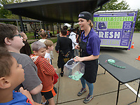 NWA Democrat-Gazette/ANDY SHUPE<br /> Ally Mrachek, director of the child nutrition department for Fayetteville Public Schools, greets fifth-grade students Wednesday, Oct. 10, 2018, before serving a hot lunch from the district food truck at Holt Middle School in Fayetteville. The food truck made its first stop in a tour of Fayetteville Public School's secondary schools in the Food Truck Dayz lunch series to raise awareness for the truck and the service it provides to promote healthy eating habits and offer meals to students in need.