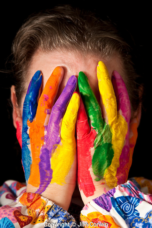 Woman hiding face behind multicolored fingers wearing a colorful clownish top