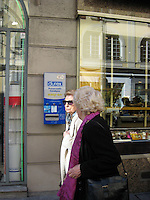 Two women pass Durex condom vending machine on wall. Monte Carlo Monaco