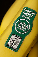 "Sticker on bananas in natural food store (Whole Foods) in the USA indicating the produce is Organic, its country of origin, and ""Fair Trade Certified"""