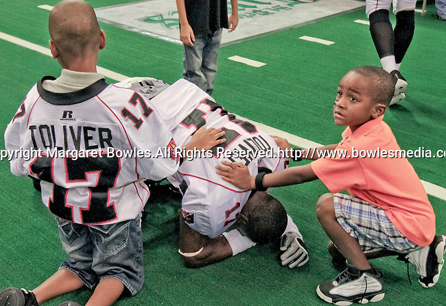 Aug 14, 2010: Orlando Predator wide receiver Antoine Toliver is overcome by emotion at the loss to Tampa Bay, as his children try to console him. The Storm defeated the Predators 63-62 to win the division title at the St. Petersburg Times Forum in Tampa, Florida. (Mandatory Credit:  Margaret Bowles)