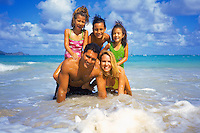 Multi-ethnic family making a pyramid at beach setting, Oahu, Hawaii
