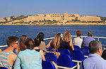 People onboard ferry boat crossing harbour from Sliema to Valletta, Malta passing Fort Manoel