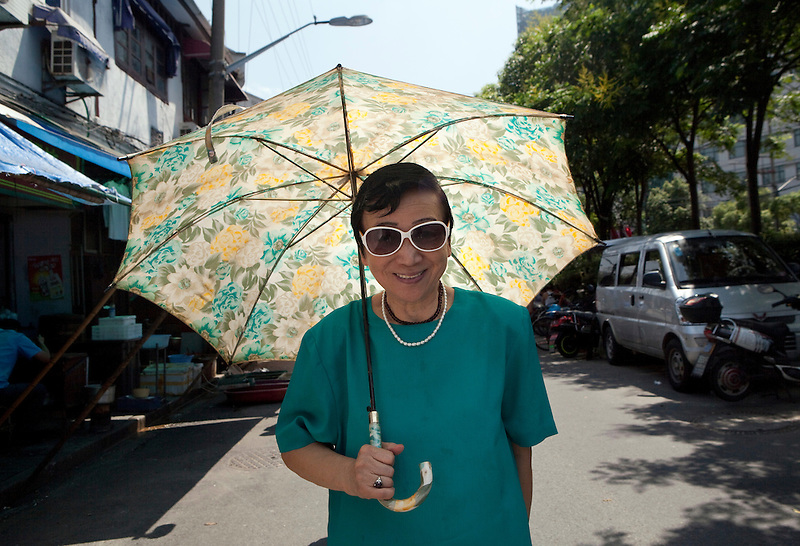 An elderly woman with sunglasses and a floral print parasol.