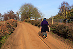 Woman walking sandy path through heathland, Suffolk Sandlings, Shottisham, Suffolk, England