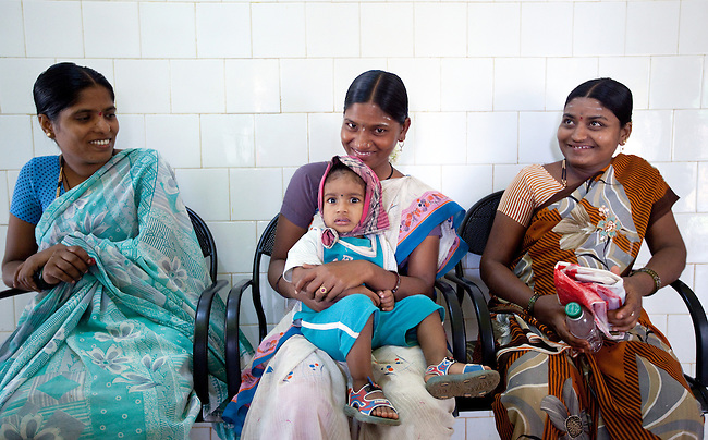 21 May 2013,  Gudageri Village, Karnartaka, India:  Nelamma (21 - centre) waits with her son Mahantesh (1.5) for treatment at the Primary Health Care centre at Gudageri Village near Hubli. The World Bank is financing the Karnataka Health Systems Project that is bringing mobile health clinics to remote villages in Karnataka and covers the cost of an ambulance, a doctor, pharmacist, two nurses, a cleaner and a driver. Villagers have the opportunity to see a doctor once a week for basic services and will be referred to Primary Health Care centres for larger issues Picture by Graham Crouch/World Bank