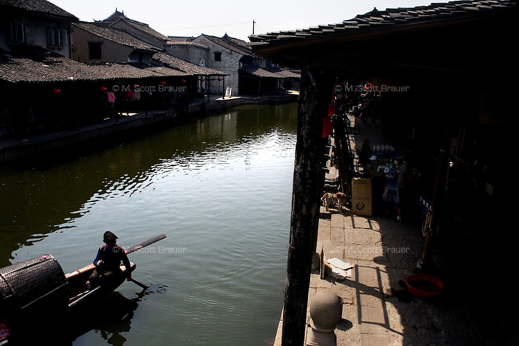 A boat operator steers and paddles with both his feet and hands in a canal Anchang, Shaoxing County, Zhejiang, China.