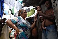 Messias Rodrigues 35 anos carrega a filha de 3 meses Michaelis Rodrigues, que está sendo cuidada em casa,  que está com dengue a mais de uma semana, confirma casos não notificados a secretaria de saude do estado, moradores na Terra firme ao lado do igarapé do Tucunduba, grande área de baixada onde pessoas moram em favelas acima dágua. Confirmado o número de notificações em 4652 casos sendo 32 de dengue hemorrágica com 8 óbitos, diz ainda que pesquisas apontam que para cada caso notificado existem 20 sem o conhecimento da saúde pública. As principais instituições envolvidas na dateção e controle da doença  são o Instituto Evandro Chagas que faz a confirmação do diagnóstico , a secretaria do estado de saúde e o hospital Barros Barreto.<br /> Belé, Pará, Brasil.<br /> 27/04/2007<br /> Foto Paulo Santos/Interfoto