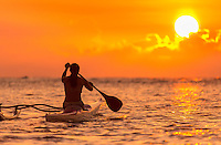 A woman ends the day with a paddling session in the waters off of Waialua, North Shore, O'ahu.