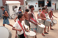 One of many young favelados who take part in the drug trade found in most Rio slums walks with an automatic rifle behind a practicing carnaval drum corps. The cocaine trade attracts many young men in the slums for the quick money it can produce.