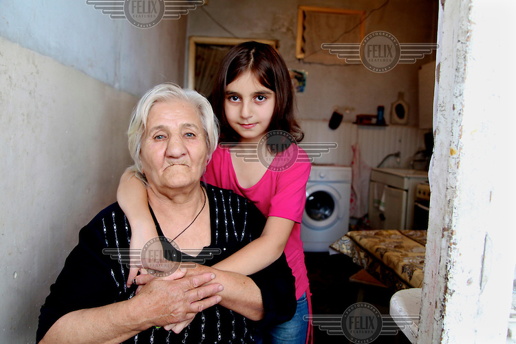 Sovinar, nine, with her grandmother who, along with her two brothers, she lives with after her mother abandoned them and her father confined to a mental hospital.