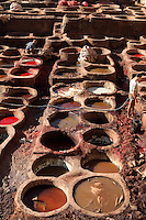 High angle view of vats, Chouara tannery, Fez, Morocco, pictured on February 22, 2009 in the morning. The Chouara tannery is the largest of the four ancient tanneries in the Medina of Fez where the traditional work of the tanners has remained unchanged since the 14th century. It is composed of numerous dried-earth pits where raw skins are treated, pounded, scraped and dyed. Tanners work in vats filled with various coloured liquid dyes derived from plant sources. Colours change every two weeks, poppy flower for red, mint for green, indigo for blue, chedar tree for brown and saffron for yellow. Fez, Morocco's second largest city, and one of the four imperial cities, was founded in 789 by Idris I on the banks of the River Fez. The oldest university in the world is here and the city is still the Moroccan cultural and spiritual centre. Fez has three sectors: the oldest part, the walled city of Fes-el-Bali, houses Morocco's largest medina and is a UNESCO World Heritage Site;  Fes-el-Jedid was founded in 1244 as a new capital by the Merenid dynasty, and contains the Mellah, or Jewish quarter; Ville Nouvelle was built by the French who took over most of Morocco in 1912 and transferred the capital to Rabat. Picture by Manuel Cohen.