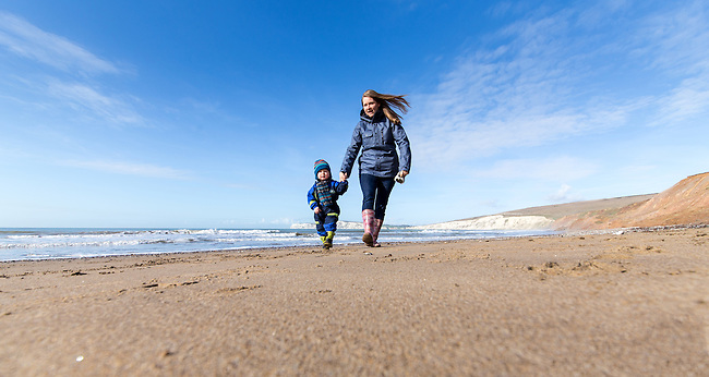 Mother and child walking on Compton Beach, Isle of Wight on a lovely bright and sunny winters day