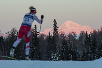 Morning light illuminates Denali as Mariah Bredel of Utah Ski Team competes in the Women's 20k Classic during the 2018 U.S. National Cross Country Ski Championships at Kincaid Park in Anchorage.