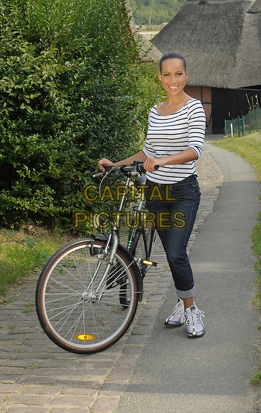 NANDINI MITRA.german moderator, privat story, surrounding area of Hamburg, Germany. .August 25th, 2009.full length white top black striped stripes jeans denim bike bicycle .CAP/RD.©Richard Dean/Capital Pictures.