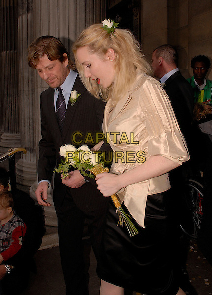 SEAN BEAN & GEORGINA SUTCLIFFE.Outside Marylebone Registry Office after their marriage ceremony, London, England, February 19th 2008..Wedding married getting hitched couple husband wife fourth time 4th half length bride groom confetti register gold wrap top shirt flowers bouquet black skirt flower in hair suit.CAP/IA.?Ian Allis/Capital Pictures
