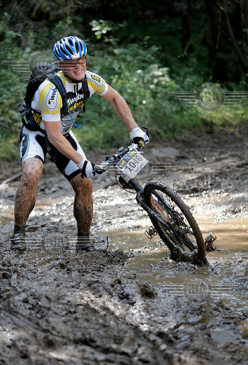A rider has to pull his bike out of a big puddle after getting stuck. Kongerittet is a mountain bike race in the forest north of the Norwegian capital Oslo. There are two courses, 64km and 84km. The interest for these kind of bike races has exploded in Norway the last few years, particularly with middle age affluent men.