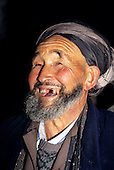 Samarkand, Uzbekistan. Portrait of a grinning old Muslim man with no front teeth, a grey beard and silver turban.