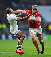 Jonathan Davies of Wales fends Jonathan Joseph of England. RBS Six Nations match between England and Wales on March 12, 2016 at Twickenham Stadium in London, England. Photo by: Patrick Khachfe / Onside Images