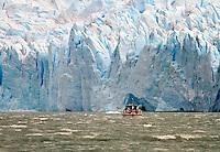 A small boat nears the massive Glacier Perito Moreno in Parque Nacionales Los Glaciares in Argentina.
