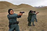 Policewomen practicing shootings at shooting range.