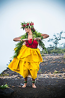 A Hawaiian cultural practitioner and dancer in traditional attire performs hula at Halema'uma'u Crater in honor of the goddess Pele, Island of Hawai'i.