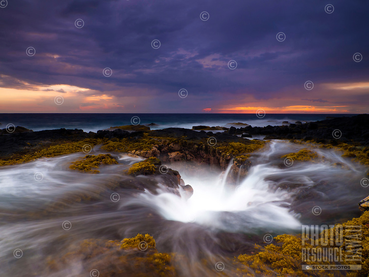With a camera's slow shutter speed at sunset, the water seems to streak through the seaweed as waves surge in and out of the blowhole at Keahole Point, Kailua-Kona, Big Island.
