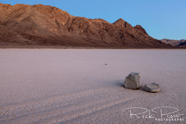 Dawn light illuminates the trail left by a sailing rock on the Racetrack Playa in Death Valley National Park is evidence of the rocks motion across the playa. The Racetrack Playa is known for its 'sailing stones' which are rocks that mysteriously move across its surface.