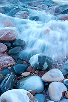 Waves on Lake Superior crashing over shoreline rocks.