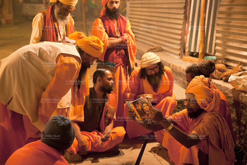 India. Uttar Pradesh state. Allahabad. Maha Kumbh Mela. A group of Sanyasins dressed with orange clothes and turban gather at night in Sangam. One man reads a book about Shiva. The Kumbh Mela, believed to be the largest religious gathering is held every 12 years on the banks of the 'Sangam'- the confluence of the holy rivers Ganga, Yamuna and the mythical Saraswati.  Sannyasa is the life stage of the renouncer within the Hindu religion. It is considered the topmost and final stage of the ashram systems and is traditionally taken by men over fifty or by young monks who wish to renounce worldly and materialistic pursuits and dedicate their lives to spiritual pursuits. People in this stage of life develop a state of dispassion and detachment from material life, renouncing worldly thoughts and desires in order to spend the remainder of their lives in spiritual contemplation. A member of the sannyasa order is known as a sannyasin (male) or sannyasini (female). The Maha (great) Kumbh Mela, which comes after 12 Purna Kumbh Mela, or 144 years, is always held at Allahabad. Uttar Pradesh (abbreviated U.P.) is a state located in northern India. 11.02.13 © 2013 Didier Ruef