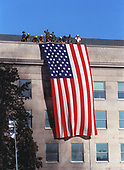 "Fire fighters and military personnel on the roof of the Pentagon unfurl a large American Flag during the September 12, 2001, visit of United States President George W. Bush to the site of the previous day's terrorist attack on the Pentagon in Washington, DC.  As the flag was draped over the wall, just south of the site where American Airlines Flight 77 impacted the building, the disaster workers gathered around the President began to sing ""God Bless America."" <br /> Credit: DoD via CNP"