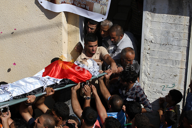 Palestinian mourners carry the body of Zakariah al-Aqrah, 21, during his funeral in the West Bank village of Qabalan near Nablus, Monday, Aug. 11, 2014. Al-Aqra was killed Monday in a shootout with Israeli forces after resisting arrest and holing up in a building in a village south of Nablus, local media reported. Photo by Nedal Eshtayah