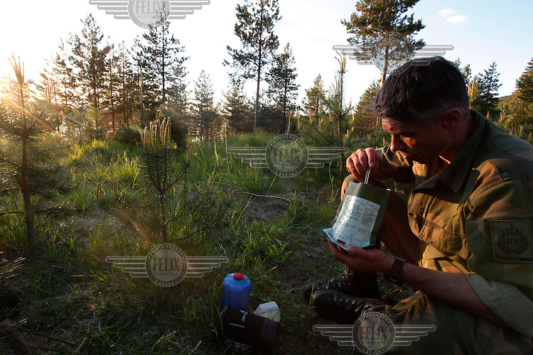 Alexander Brodahl Moxnes eats MRE (Meals Ready to Eat) outside his tent as the sun sets. Norwegian Home Guard soldiers during exercise Djerv..The Home Guard has traditionally been designated to secure important  domestic installations in case of war or crisis. With the cold war long gone, a war in Afghanistan and budget cuts, there is a debate over the Home Guard's role in the future.