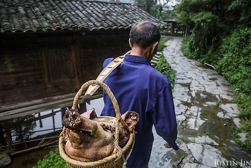 A man carries a pig's head to a temple in Dimen.