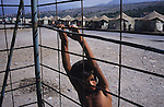 A boy hangs of a wire fence in the infamous Konik refugee camp, where Kosovar Roma refugees were all but forgotten after the war, living on meagre handouts and sheltering in all weathers in a UNHCR tent village long after the Kosovo war had ended. Podgerica, Montenegro 1999.