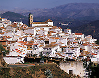 The church-steeple rises above the pretty white village of Algotocin, southern Spain, with a background of distant hills.