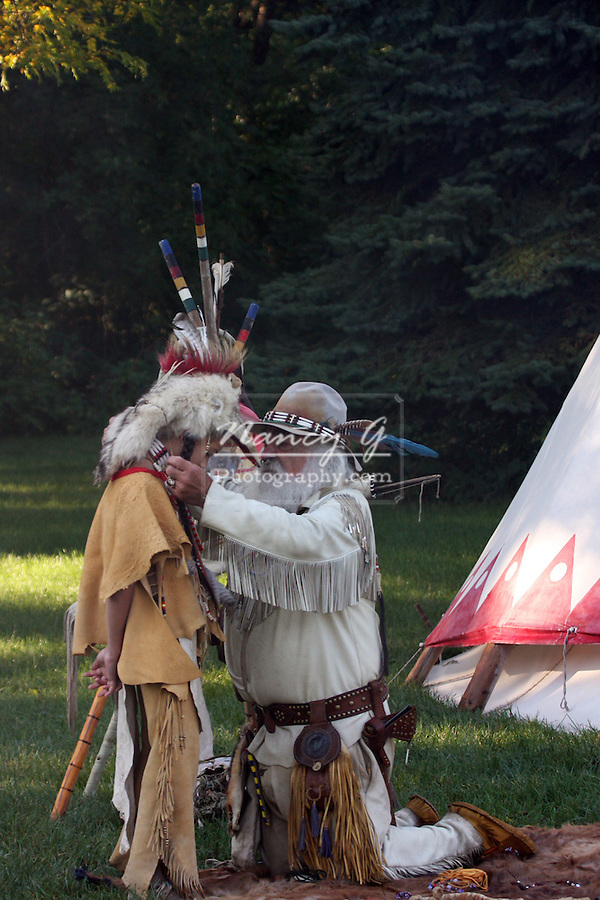 A young Native American Indian boy receiving a gift of a necklace from a mountain man by a tipi